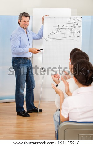 Business People Applauding The Male Lecturer At The End Of A Training Class Or Presentation - stock photo