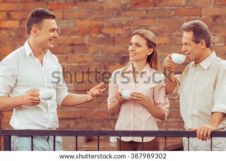Business people are discussing business affairs, drinking coffee and tea and smiling during business lunch at the balcony of the restaurant - stock photo