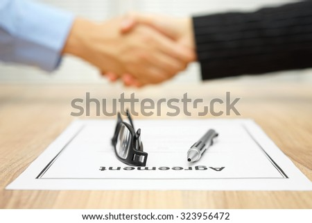 Business people are handshaking over signed agreement,focus on  document - stock photo