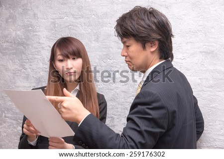 business people are talking in front of a wall,  supervisor is directing businesswoman at the work - stock photo