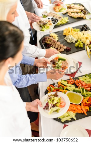 Business people around buffet table catering food at company event - stock photo