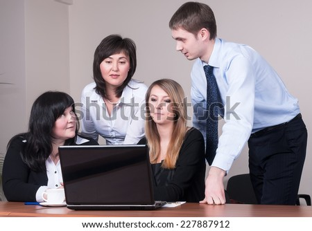 Business people arranged brainstorming behind the laptop at office - stock photo