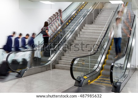 Business people at rush hour on a moving escalators motion blur