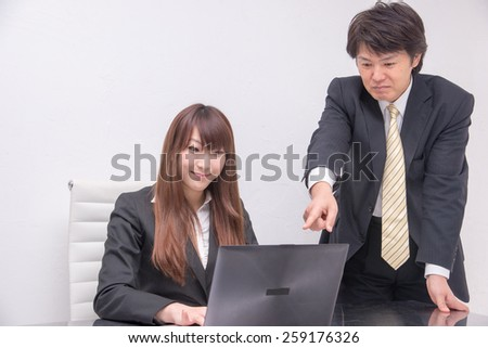 business people at the desk, supervisor is directing businesswoman at the desk and operating computer - stock photo