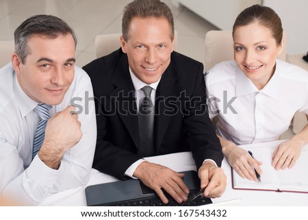 Business people at work. Top view of three cheerful business people in formalwear sitting at the table and looking at camera