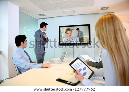 Business people attending videoconference meeting - stock photo