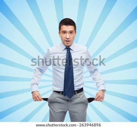 business, people, bankruptcy and failure concept - surprised businessman showing empty pockets over blue burst rays background - stock photo