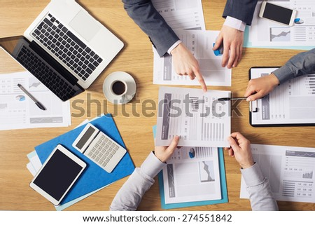 Business people brainstorming at office desk, they are analyzing financial reports and pointing out financial data on a sheet, top view - stock photo