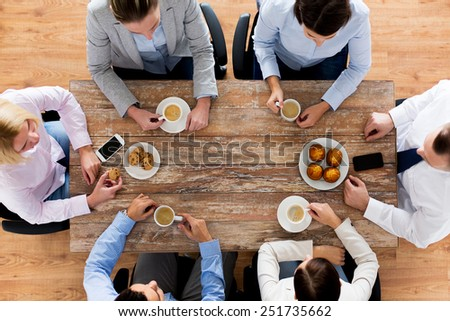 business, people, break and team work concept - close up of creative team meeting and drinking coffee with muffins during lunch in office - stock photo