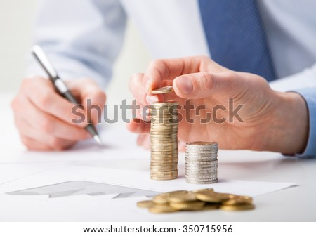 Business people calculating profit - closeup shot of hands counting coins and making notes on paper