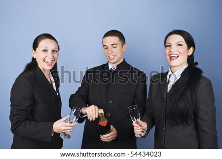 Business people celebrating their success with champagne ,women laughing and cheering while the man open the bottle of champagne - stock photo