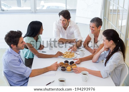 Business people chat while eating muffins and drinking coffee in the office - stock photo