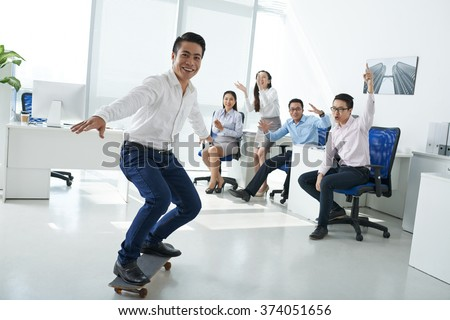 Business people cheering when their colleague skateboarding in the office