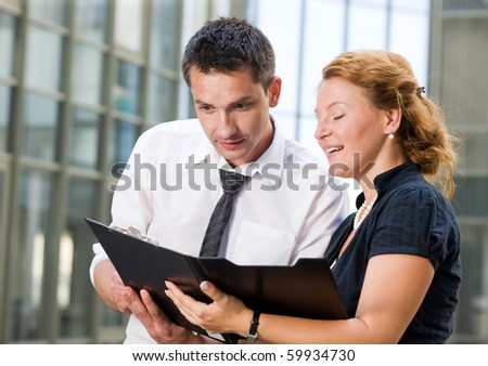 Business people communicating in front of office building and trying to sign the contract between two companies. Red-haired woman smiling and showing documents to his partner. - stock photo
