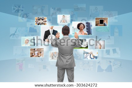 business, people, communication, technology and connection concept - businessman working with images on virtual screen over blue background from back - stock photo