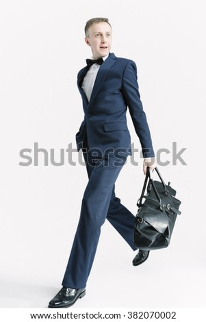 Business People Concepts. Young Caucasian Handsome Man With Bag Striding Against White. Vertical Image Orientation - stock photo