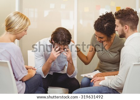 Business people consoling businessman suffering from headache in office - stock photo