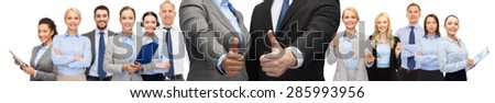 business, people, cooperation, success and gesture concept - businessman and businesswoman showing thumbs up over group of office team background - stock photo