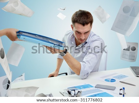 business, people, deadline and paperwork concept - businessman taking folder from secretary over blue background and falling papers