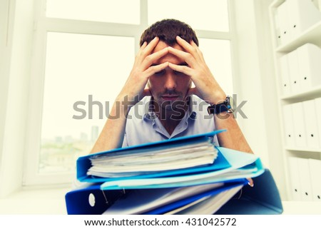 business, people, deadline, stress and paperwork concept - sad businessman with stack of folders at office - stock photo