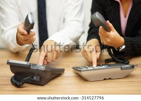 business people dialing on land line telephone to contact clients - stock photo