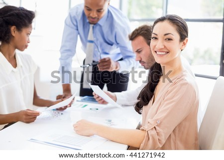 Business people discussing a report at meeting in office - stock photo