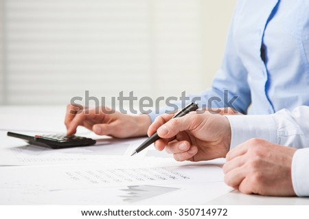 Business people discussing financial charts - closeup shot of hands over table - stock photo