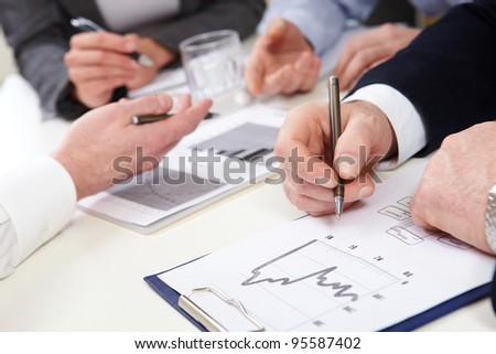 Business people discussing graphs and diagrams - stock photo
