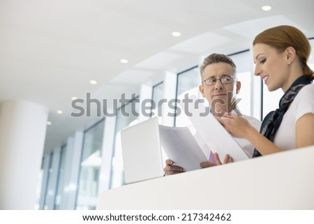 Business people discussing over documents in office - stock photo