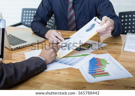 Business people discussing the charts and graphs showing the results of their successful teamwork. - stock photo