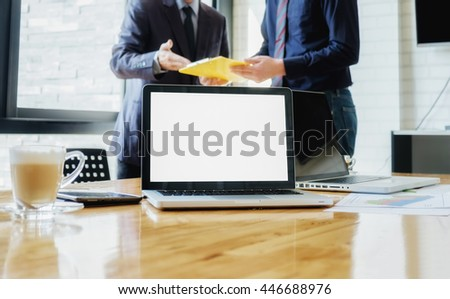 Business people discussing the charts and graphs showing the results of their successful teamwork. Laptop computer with blank white screen ready for content on wooden desk. Business concept. - stock photo