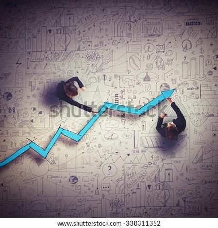 Business people draw a big arrow uphill - stock photo