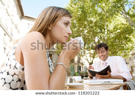 Business people drinking coffee and using technology while sitting at a coffee shop terrace outdoors, in a classic office buildings city, smiling.
