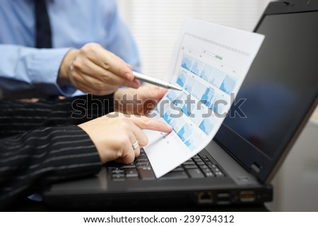 Business people  during meeting  discussing and pointing  to financial diagram, graphs - stock photo