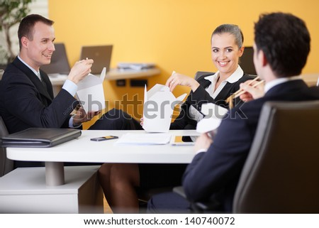 Business people eating Chinese food in the office during lunch break - stock photo