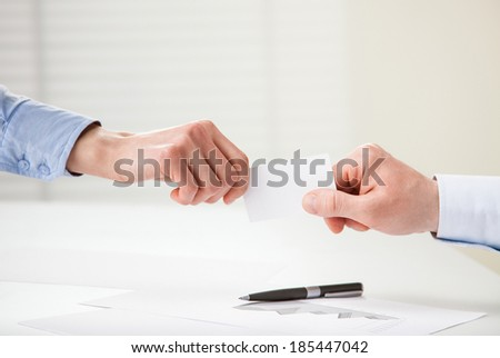 Business people exchanging card - closeup shot of hands - stock photo