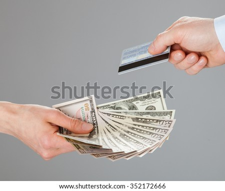 Business people exchanging credit card and money - closeup shot of hands