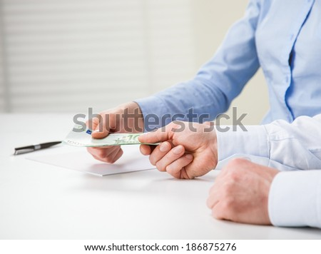 Business people exchanging euro banknotes - closeup shot of hands - stock photo