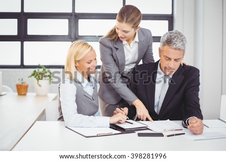 Business people explaining client with documents at desk in office - stock photo