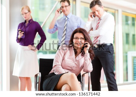 Business people - female boss and employees in office, all making a call with their mobiles - stock photo