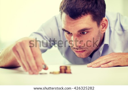 business, people, finances and money saving concept - businessman putting coins into piles at office - stock photo