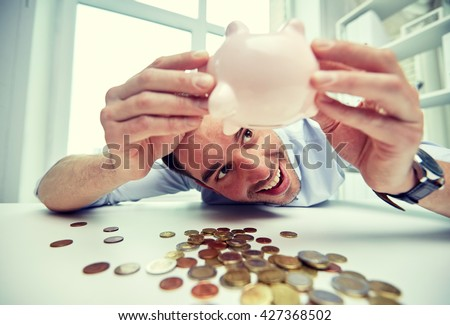 business, people, finances and money saving concept - happy businessman shaking piggy bank and getting coins at office - stock photo
