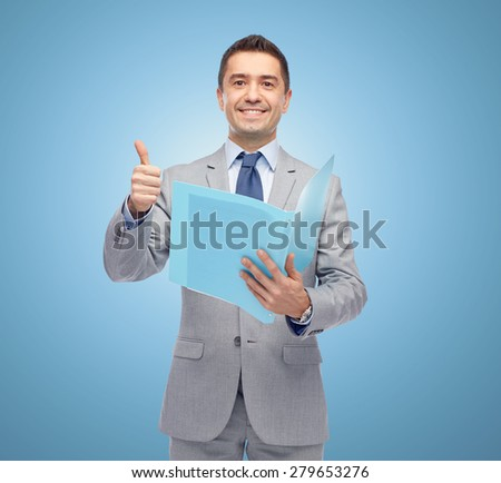 business, people, finances and paper work concept - happy smiling businessman in suit holding folder and showing thumbs up over blue background - stock photo