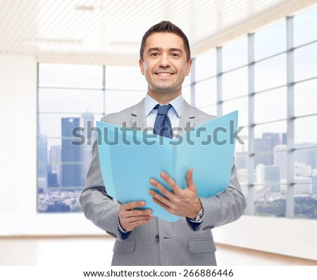 business, people, finances and real estate concept - happy smiling businessman in suit holding open folder over office room with big window and city view background - stock photo