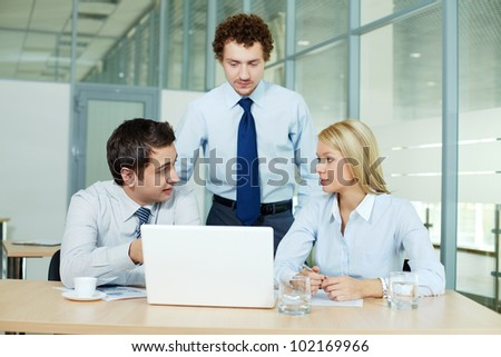 Business people gathered in office in front of laptop - stock photo