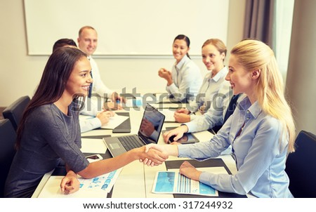 business, people, gesture and partnership concept - smiling business team with laptop computer and papers shaking hands in office - stock photo