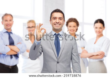 business, people, gesture and success concept - happy smiling businessman in suit with team over office room background showing ok hand sign - stock photo