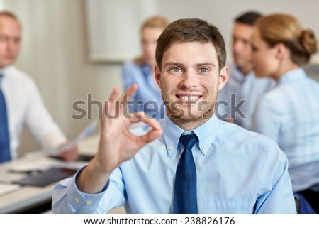 business, people, gesture and teamwork concept - smiling businessman showing ok gesture with group of businesspeople meeting in office - stock photo