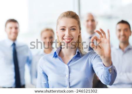 business, people, gesture and teamwork concept - smiling businesswoman showing ok sign with group of businesspeople in office - stock photo