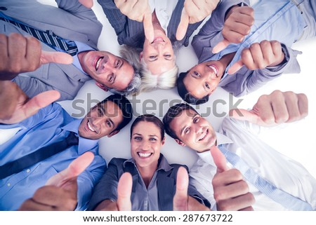 Business people gesturing thumbs up on white background - stock photo